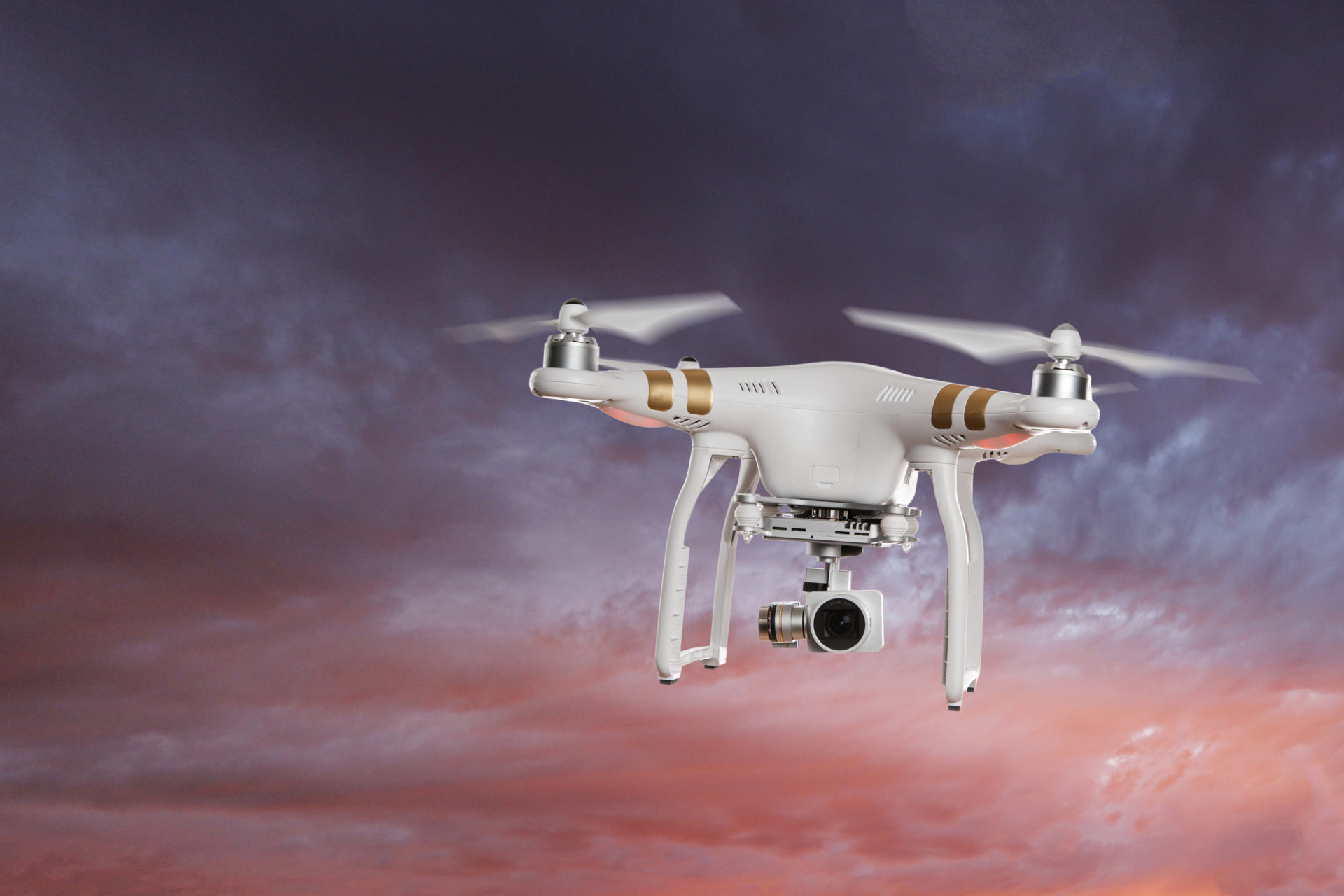 White drone quad copter with high resolution digital camera flying in the blue sky.
